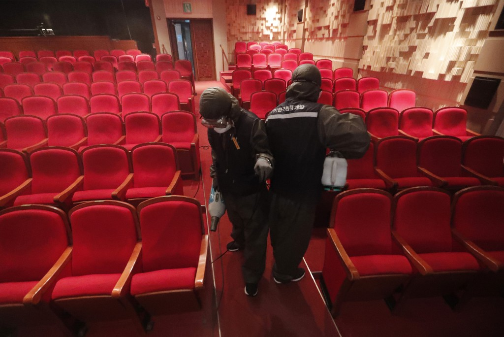 Workers wearing protective gears spray disinfectant as a precaution against a new coronavirus at a theater in Sejong Center in Seoul, South Korea, Tue...