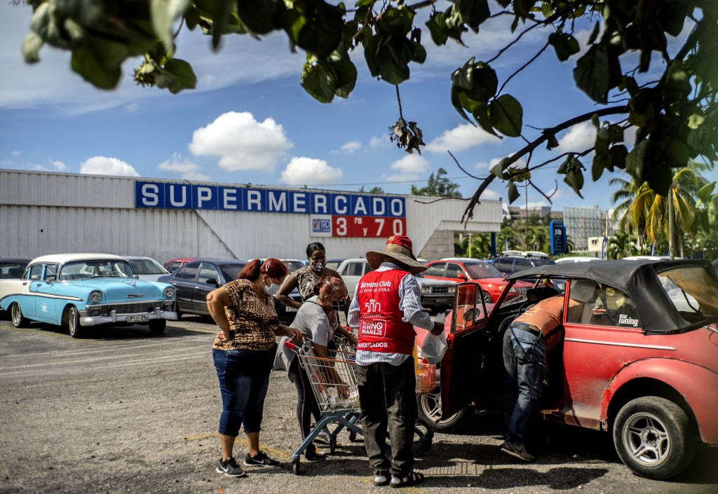 Shoppers wearing protective facemasks amid the spread of the new coronavirus load groceries from a dollar store in Havana, Cuba, Monday, July 20, 2020...