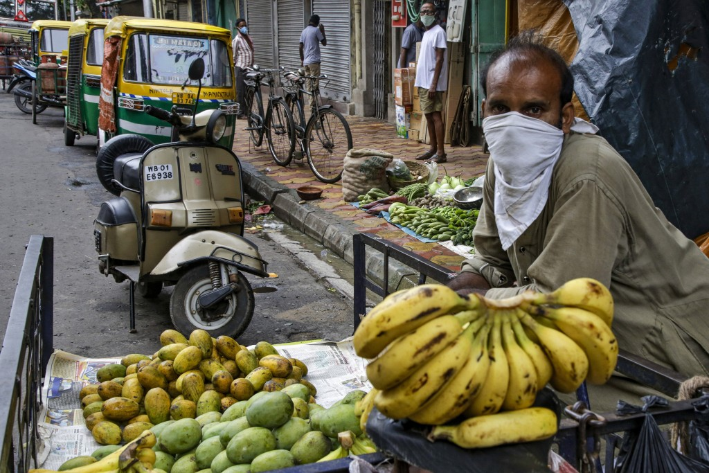 A street side fruit vendor has his face covered as a precaution against the coronavirus in Kolkata, India, Tuesday, July 21, 2020. With a surge in cor...