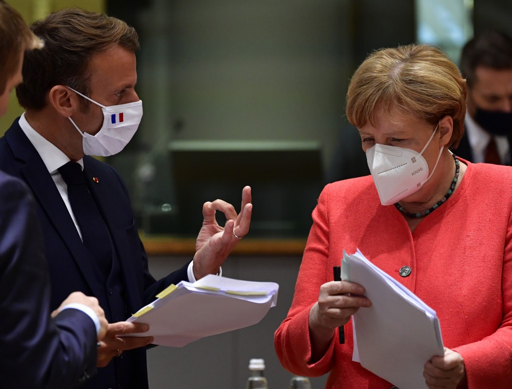 German Chancellor Angela Merkel, right, looks over papers with French President Emmanuel Macron during a round table meeting at an EU summit in Brusse...