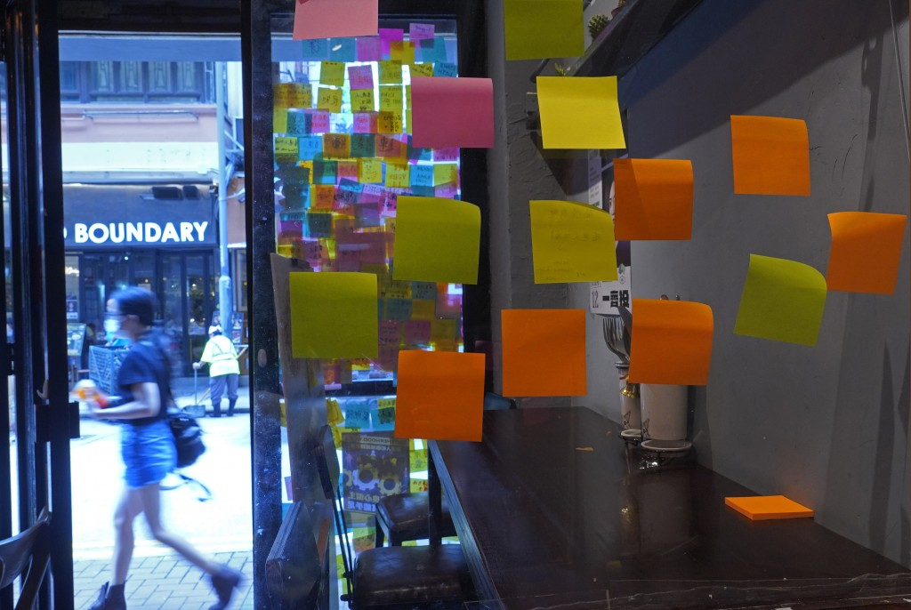 "A Hong Kong Cafe, known as a ""yellow shop"" because its owners expressed sympathy for protesters, has windows decorated with blank post-it notes in Hon..."