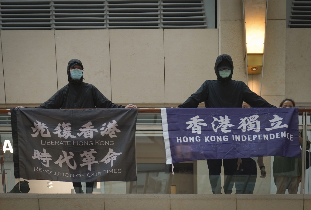"FILE - In this June 9, 2020, file photo, protesters show a banner ""Librate Hong Kong, Revolution of out time,"" left, and ""Hong Kong Independence"" in a..."
