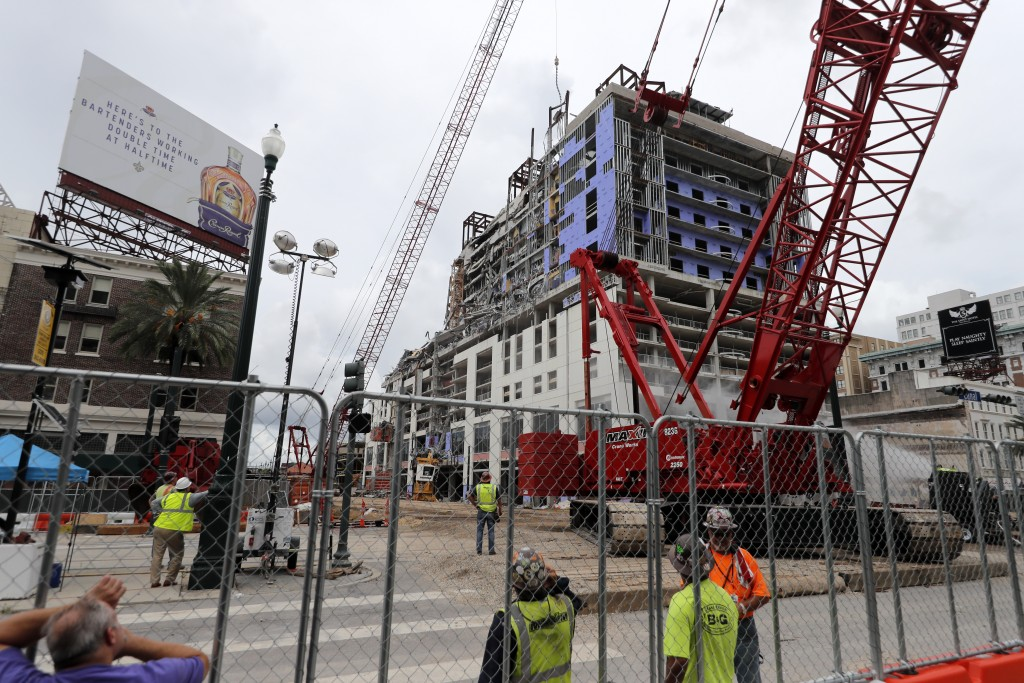 Workers watch as a wrecking ball knocks debris loose from the Hard Rock Hotel building collapse site in New Orleans, Monday, July 20, 2020. New Orlean...