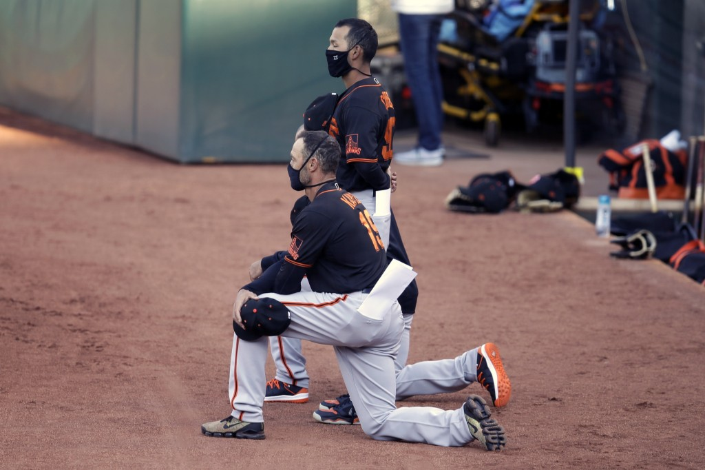San Francisco Giants' manager Gabe Kapler kneels during the national anthem prior to an exhibition baseball game against the Oakland Athletics, Monday...