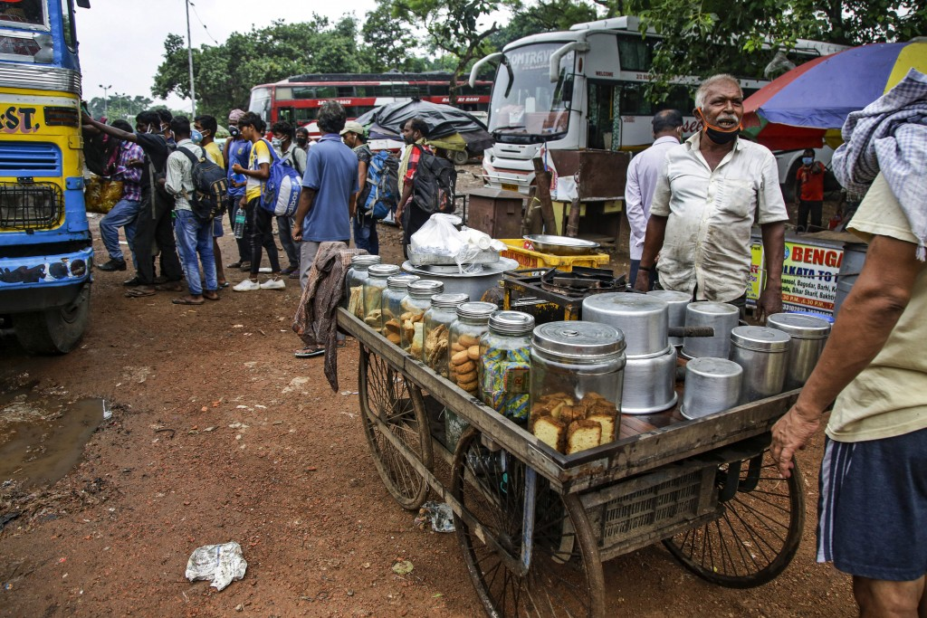 A tea seller with a face mask hanging on his chin talks to a customer beside his movable cart as commuters jostle for a ride on a bus discarding socia...
