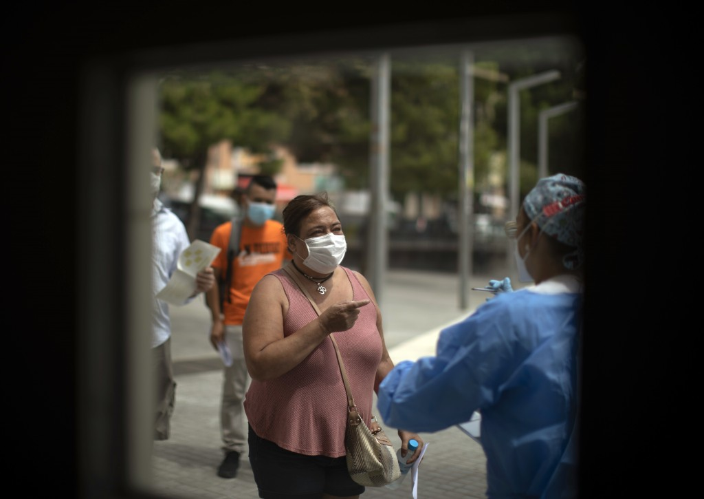 FILE - In this Tuesday, July 14, 2020 file photo, a health worker receives patients outside a local hospital in Hospitalet, outskirts of Barcelona, Sp...