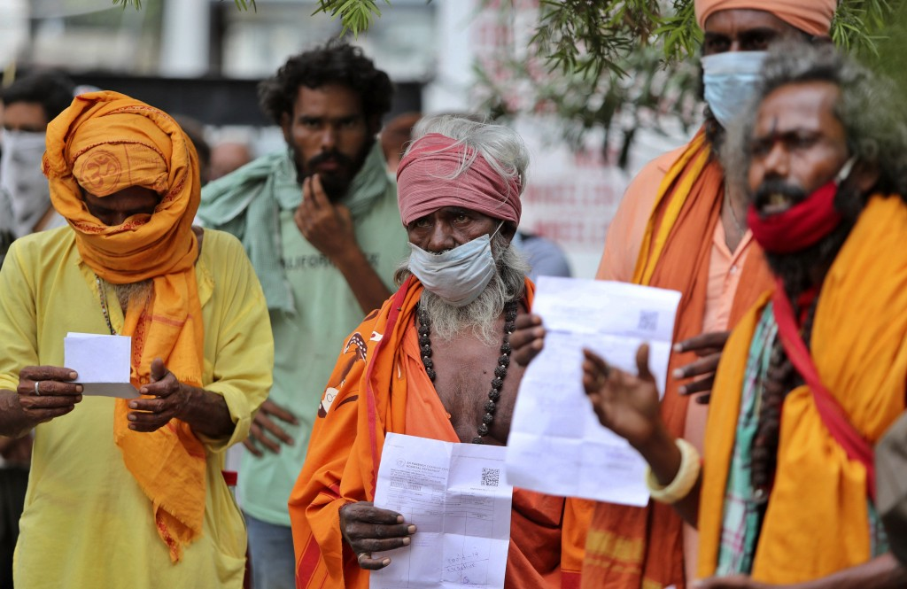 Hindu holy men wearing face masks wait to consult doctors at a COVID-19 screening facility inside a government hospital in Jammu, India, Tuesday, July...