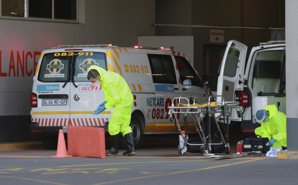 A paramedic in personal protective equipment is seen at an ambulance outside the Christiaan Barnard Memorial Hospital in Cape Town, South Africa, Tues...
