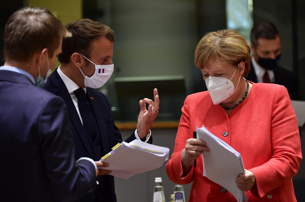 German Chancellor Angela Merkel, right, speaks with French President Emmanuel Macron, center, during a round table meeting at an EU summit in Brussels...