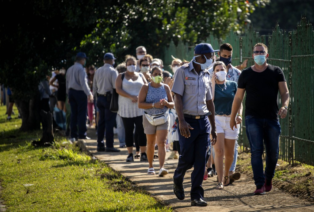 People wearing protective face masks as a precaution amid the spread of the new coronavirus line up to enter a grocery store that accepts U.S. dollars...