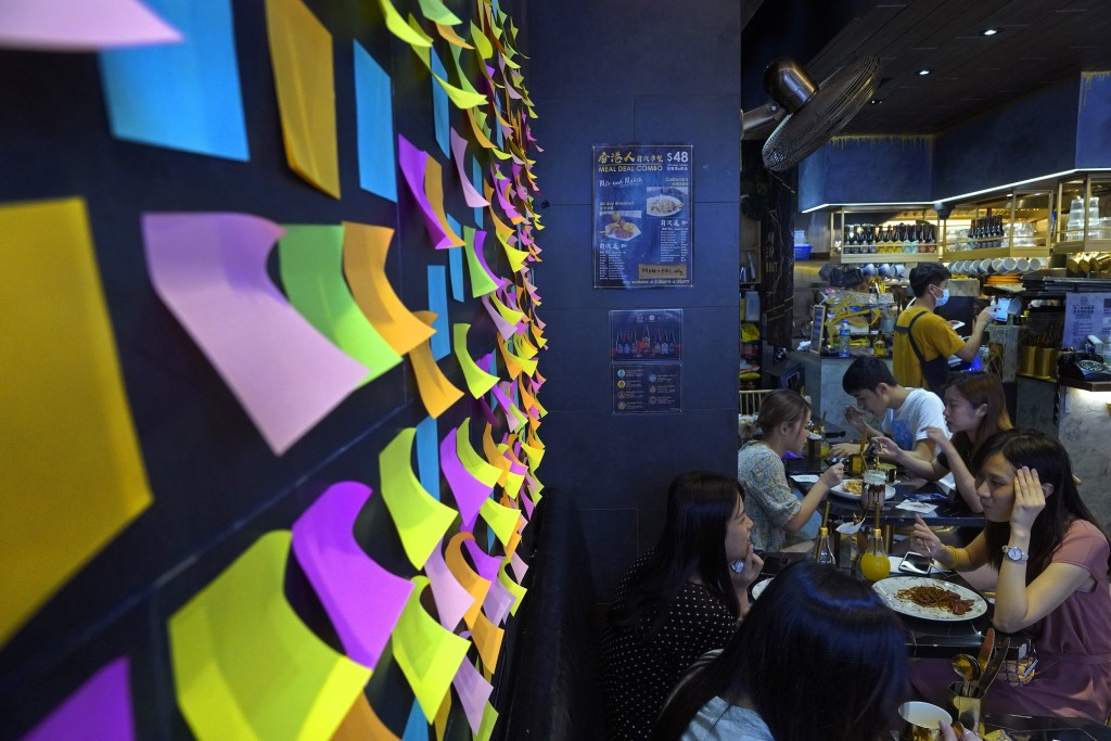 "A Hong Kong Cafe, known as a ""yellow shop"" because its owners expressed sympathy for protesters, has a wall decorated with blank post-it notes in Hong..."