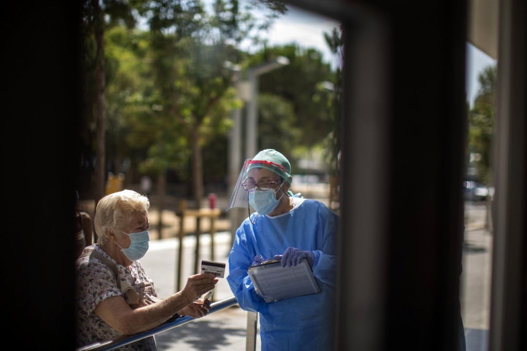 FILE - In this Tuesday, July 14, 2020 file photo, a health worker receives a patients at a local hospital in Hospitalet, outskirts of Barcelona, Spain...