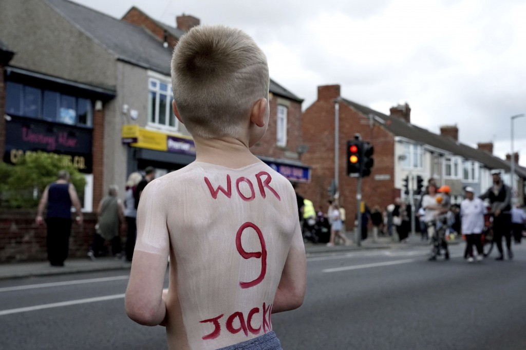 People line the streets as the funeral cortege of former England soccer player Jack Charlton passes through his hometown of Ashington, in Northumberla...