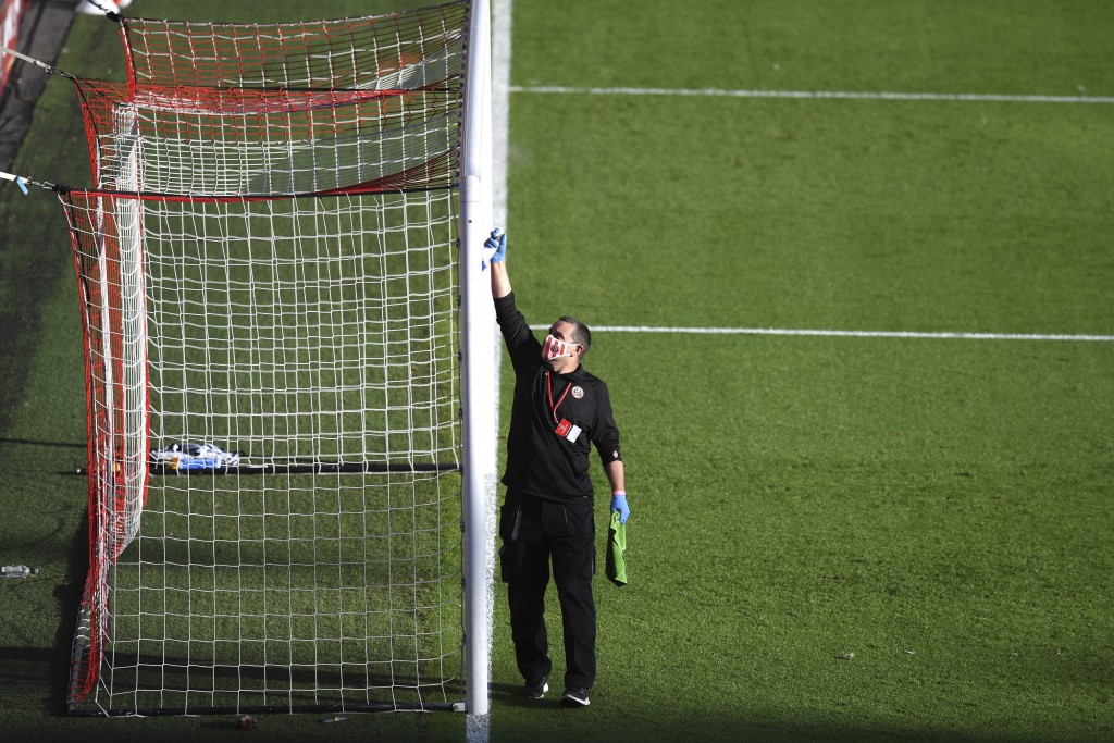 A grounds crew member cleans the goal posts during a water break in the English Premier League soccer match between Sheffield United and Everton at Br...
