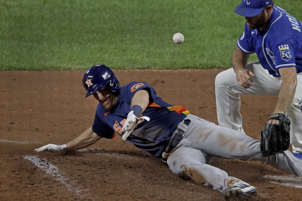 Houston Astros' Myles, left, Straw beats the tag at home by Kansas City Royals relief pitcher Greg Holland to score on a wild pitch during the seventh...