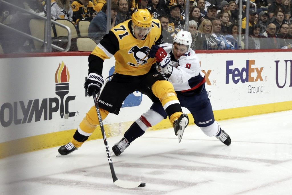 FILE - In this March 7, 2020, file photo, Pittsburgh Penguins' Evgeni Malkin (71) controls the puck as Washington Capitals' Dmitry Orlov (9) defends d...