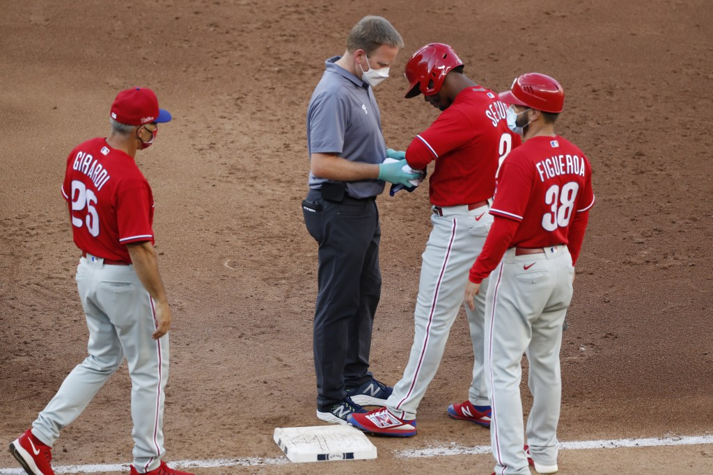 Philadelphia Phillies manager Joe Girardi, left, approaches first base as a trainer examines Phillies Jean Segura (2) for an injury after he was hit b...