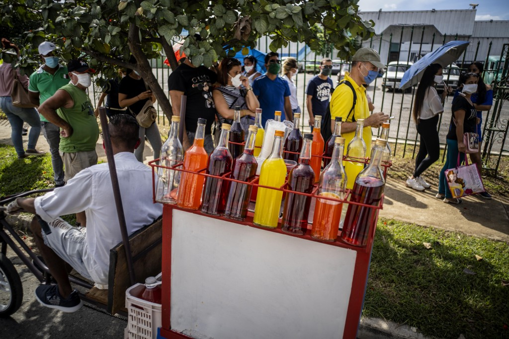 A snow cone vendor looks for customers amid a line of people, all wearing protective face masks as a precaution during the spread of the new coronavir...
