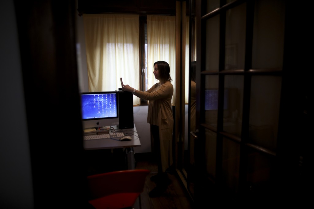 Psychologist Maria Clara Benitez text messages in the room where she attends patients online at her home during a government-ordered lockdown to curb ...