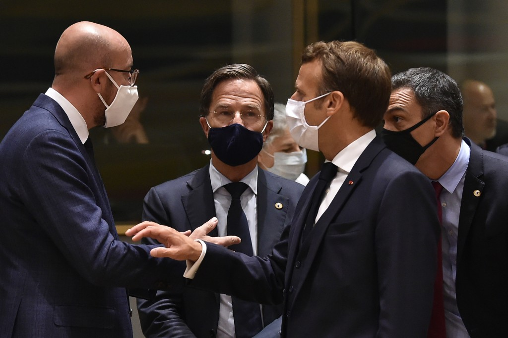 European Council President Charles Michel, left, speaks with French President Emmanuel Macron, second right, and Dutch Prime Minister Mark Rutte, seco...