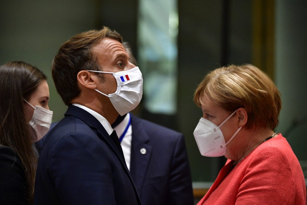 From left, Finland's Prime Minister Sanna Marin, French President Emmanuel Macron and German Chancellor Angela Merkel attend a round table meeting at ...