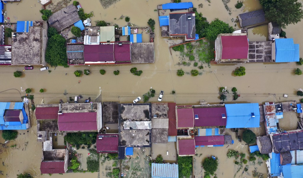 In this photo released by Xinhua News Agency, an aerial photo shows the extent of flooding in Guzhen Town of Lu'an City in eastern China's Anhui Provi...