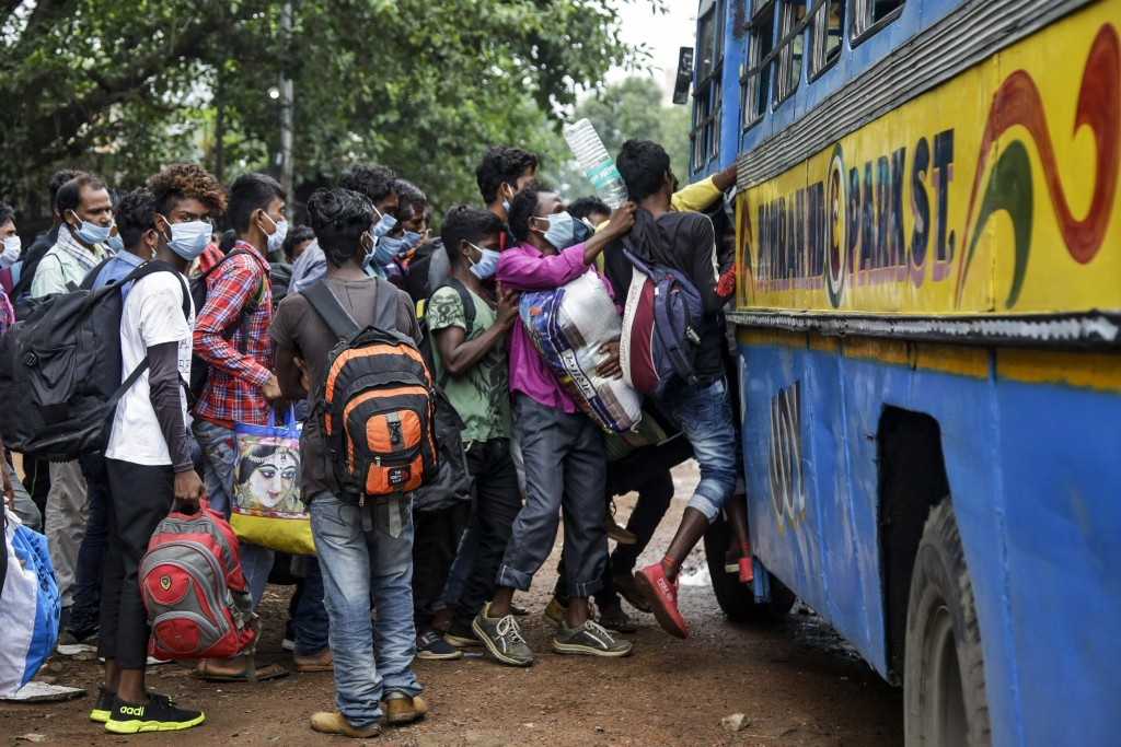 Commuters wearing face masks jostle for a ride on a bus discarding social distancing guidelines in Kolkata, India, Tuesday, July 21, 2020. With a surg...