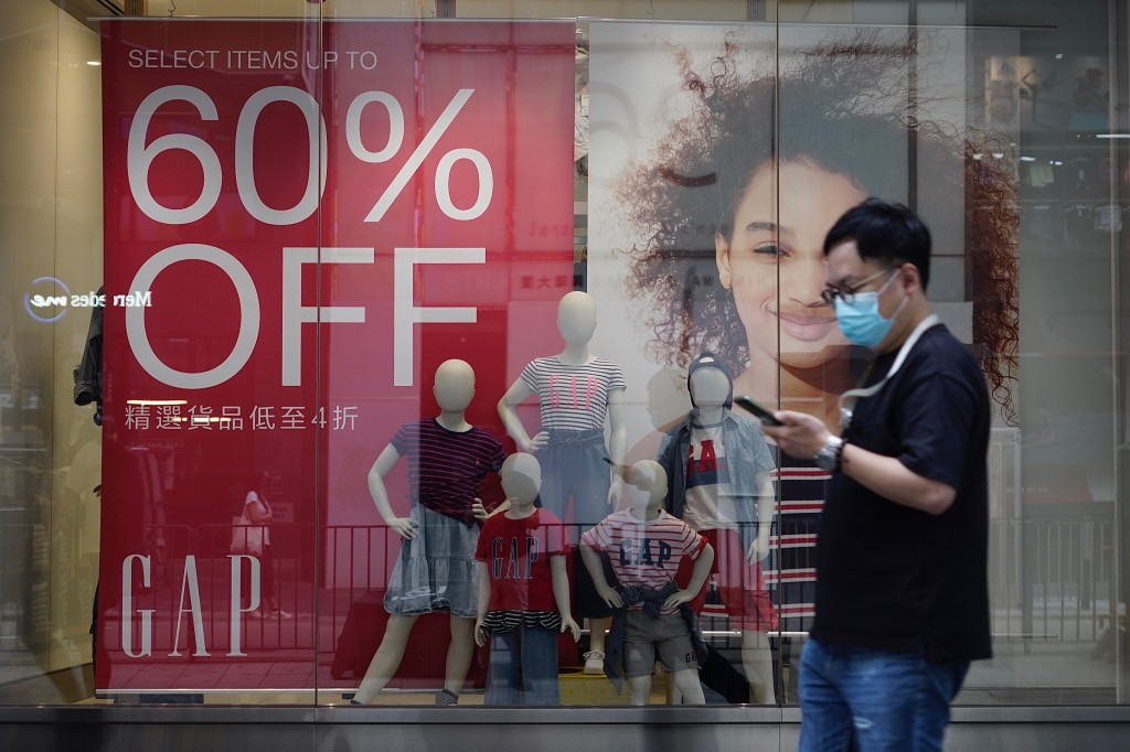 A man wearing a face mask to protect against the new coronavirus walks past a shop with sales discount sign in Hong Kong Tuesday, July 21, 2020. Hong ...