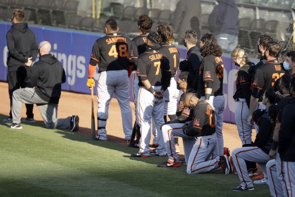San Francisco Giants' Antoan Richardson (00) and Jaylin Davis kneel during the national anthem prior to an exhibition baseball game against the Oaklan...