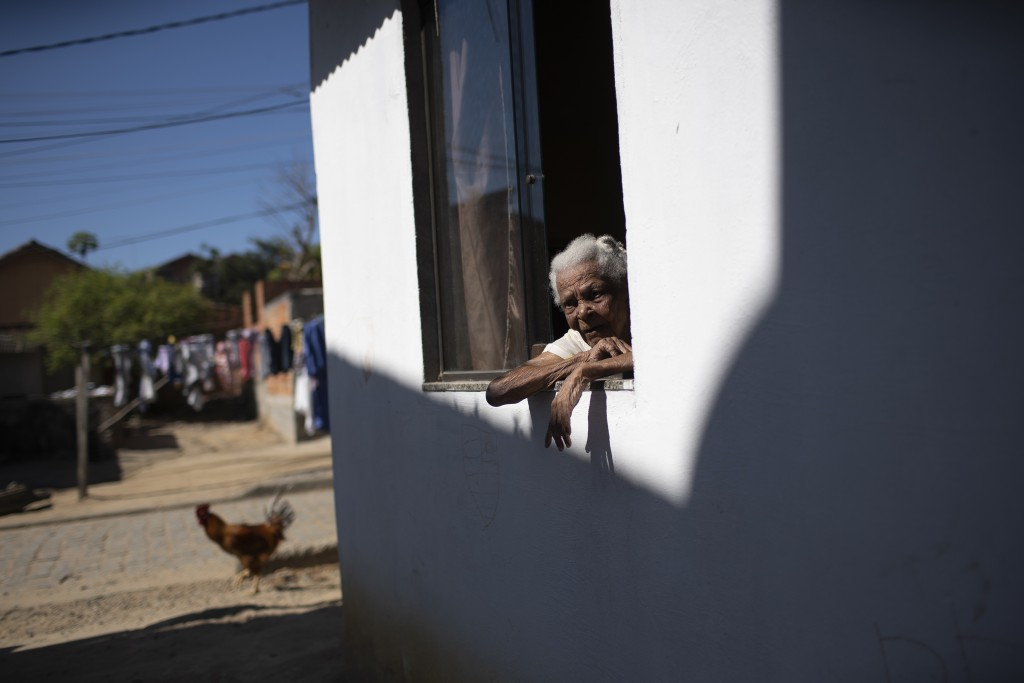 """Eva Maria de Jesus, also known as """"Avo Eva"""" or Grandmother Eva, 110, looks from a window of her home at the Rasa """"Quilombo"""" in Buzios, Brazil, Sunday,..."""