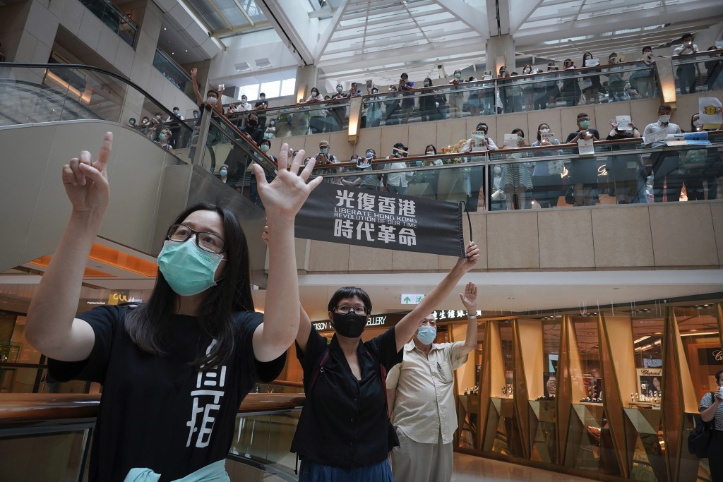 "FILE - In this June 9, 2020, file photo, protesters show a banner ""Librate Hong Kong, Revolution of out time"" and gesture with five fingers, signifyin..."