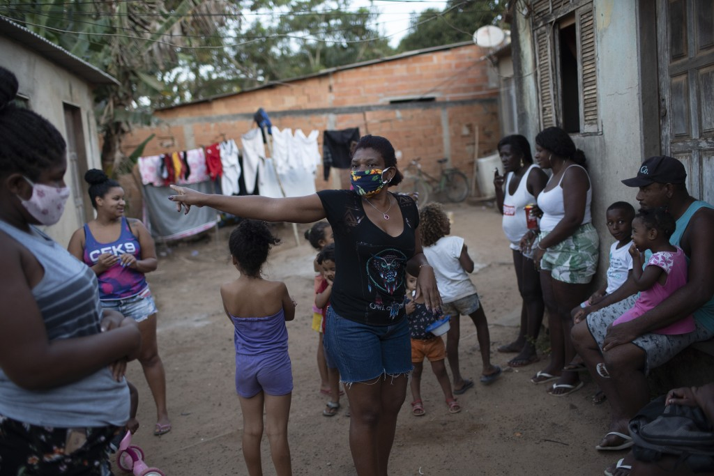 Residents gather as donated food, kits of cleaning products and protective face masks are distributed amid the new coronavirus pandemic at the Maria J...