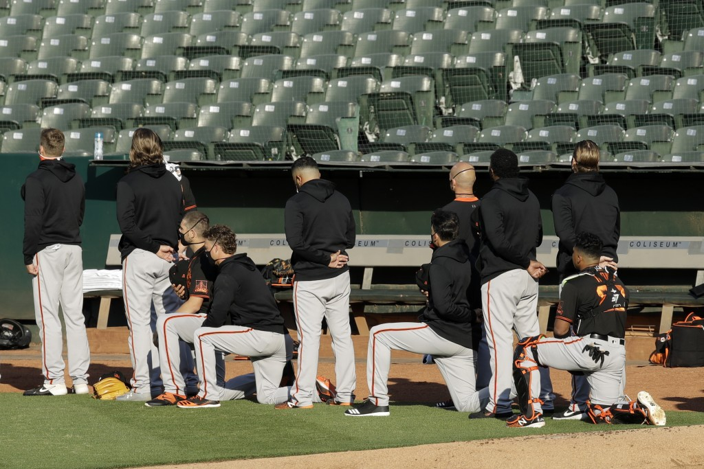 Some San Francisco Giants kneel during the national anthem prior to an exhibition baseball game against the Oakland Athletics on Monday, July 20, 2020...