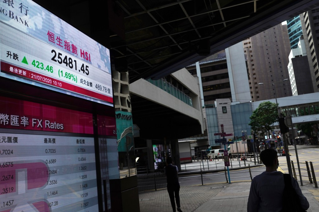 A man wearing a face mask walks past a bank's electronic board showing the Hong Kong share index in Hong Kong Tuesday, July 21, 2020. Asian shares wer...