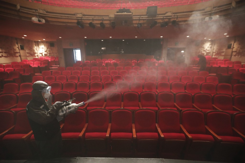 A worker wearing a protective gear sprays disinfectant as a precaution against a new coronavirus at a theater in Sejong Center in Seoul, South Korea, ...