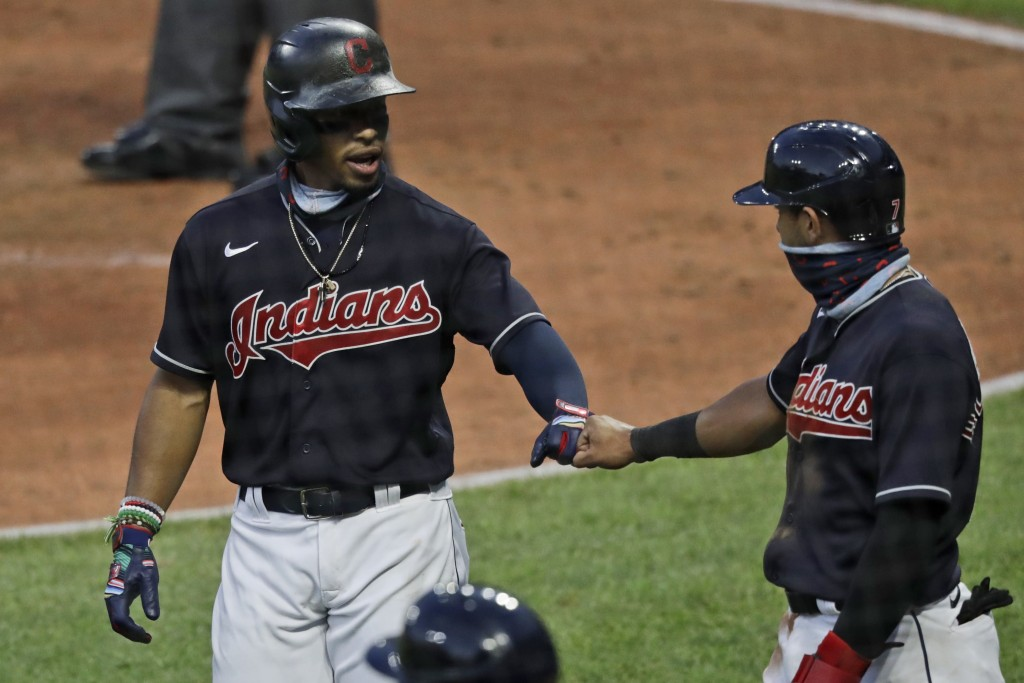 Cleveland Indians' Francisco Lindor, left, is congratulated by Cesar Hernandez after hitting a three-run home run in the fifth inning during a preseas...