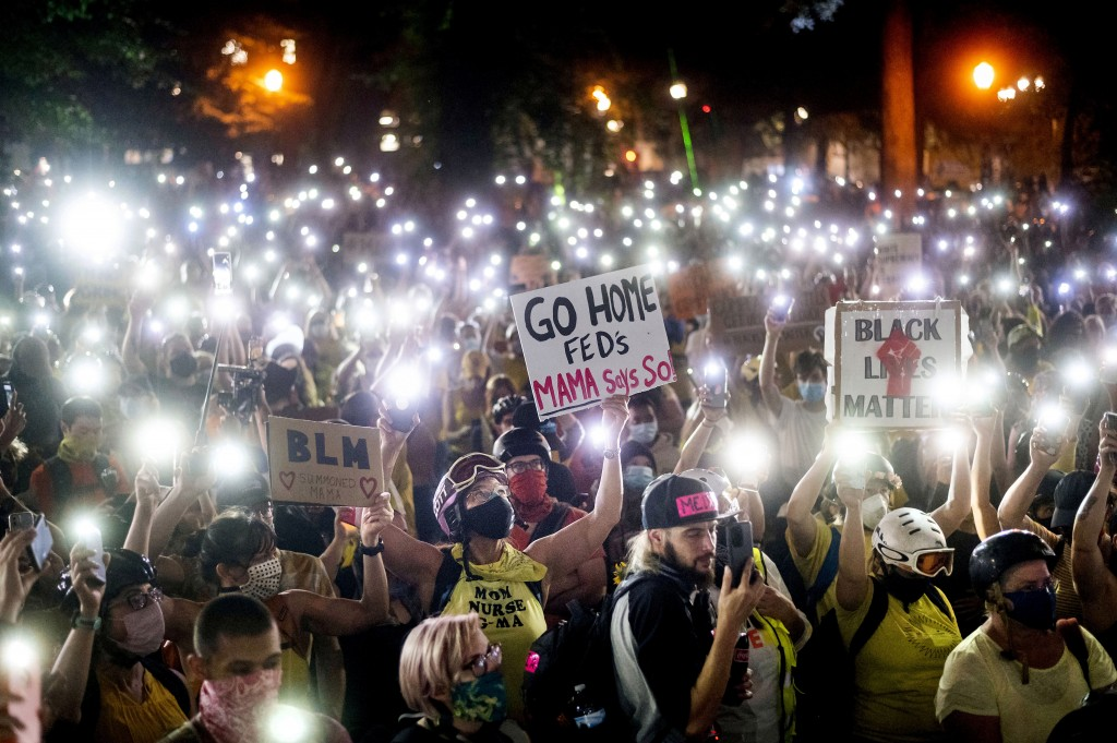 Hundreds of Black Lives Matter protesters hold their phones aloft on Monday, July 20, 2020, in Portland, Ore.  Federal officers' actions at protests i...