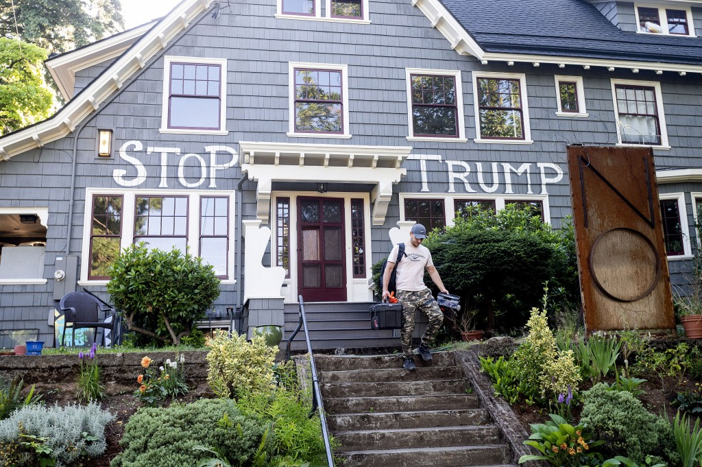 "A worker, who declined to give his name, leaves a Portland, Ore., home that features a ""STOP TRUMP"" sign on Monday, July 20, 2020. Following the death..."