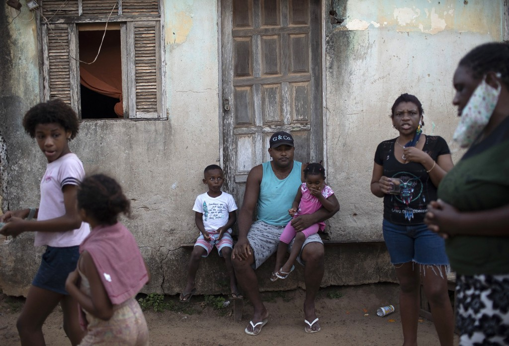 """Residents of the Maria Joaquina """"Quilombo"""" wait for the distribution of donated food, kits of cleaning products and protective face masks, amid the ne..."""