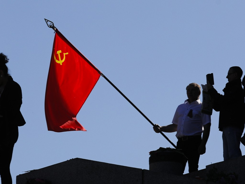 FILE - In this file photo dated Saturday, May 9, 2020, a man holds a Soviet flag during a ceremony at the Soviet War memorial to mark the 75th anniver...