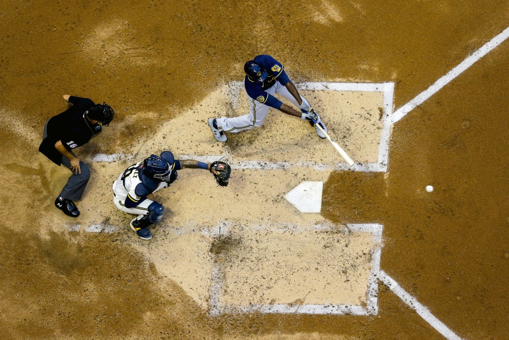 FILE - In this July 14, 2020, file photo, Milwaukee Brewers' Lorenzo Cain, right, hits a single during an intrasquad game at Miller Park in Milwaukee....