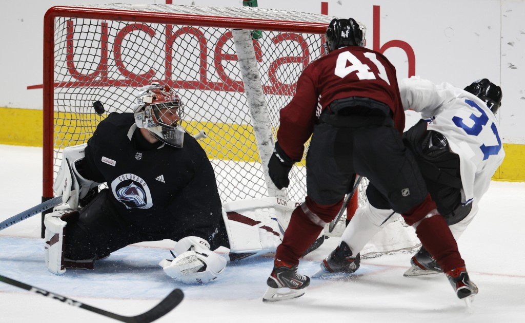 Colorado Avalanche left wing J.T. Compher, right, scores a goal against goaltender Philipp Grubauer, left, while being checked by center Pierre-Edouar...
