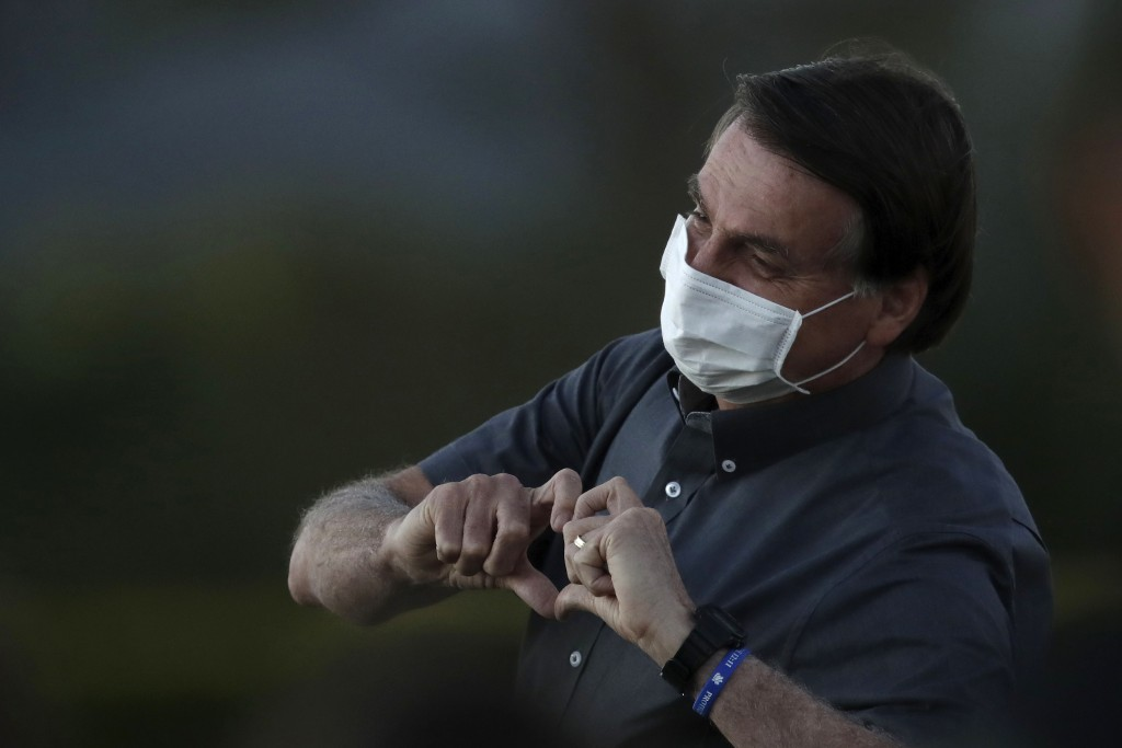 Brazil's President Jair Bolsonaro who is infected with COVID-19, wears a protective face mask as he makes a heart sign to supporters during a Brazilia...