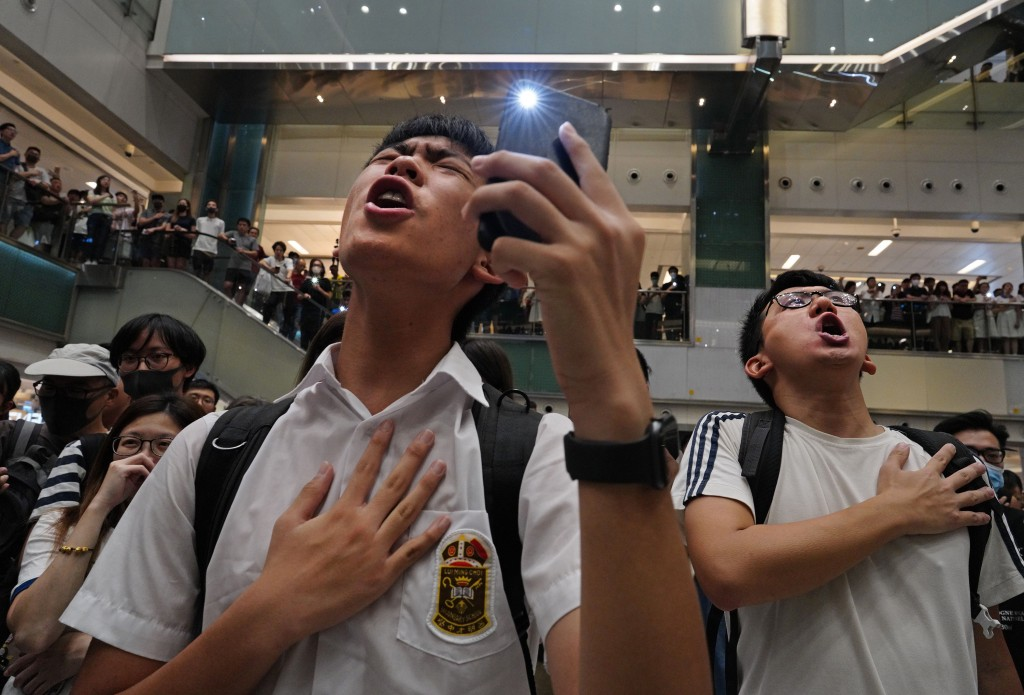 """FILE - In this Sept. 11, 2019, file photo, local residents sing a theme song written by protesters """"Glory be to thee"""" at a shopping mall in Hong Kong...."""