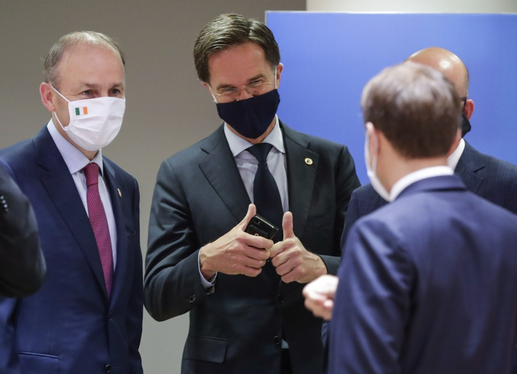Dutch Prime Minister Mark Rutte, center, gives the thumbs up as he speaks with French President Emmanuel Macron, right, and Ireland's Prime Minister M...