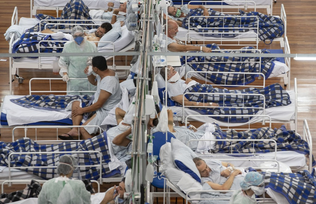 FILE - In this June 9, 2020, file photo COVID-19 patients lie on beds in a field hospital built inside a gym in Santo Andre, on the outskirts of Sao P...