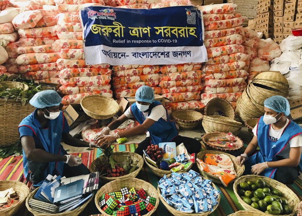 FILE - In this June 6, 2020, file photo, members of Bidyanondo Foundation volunteers pack care packages for COVID-19 patients in Dhaka, Bangladesh. A ...