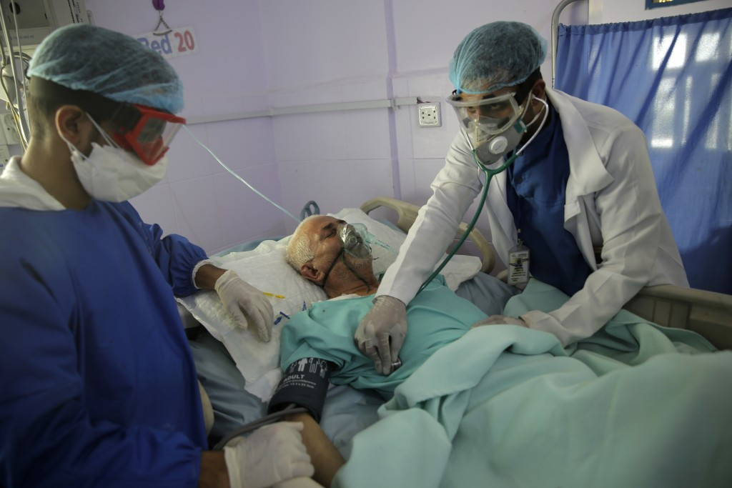 FILE - In this June 14, 2020, file photo, medical workers attend to a COVID-19 patient in an intensive care unit at a hospital in Sanaa, Yemen. A new ...