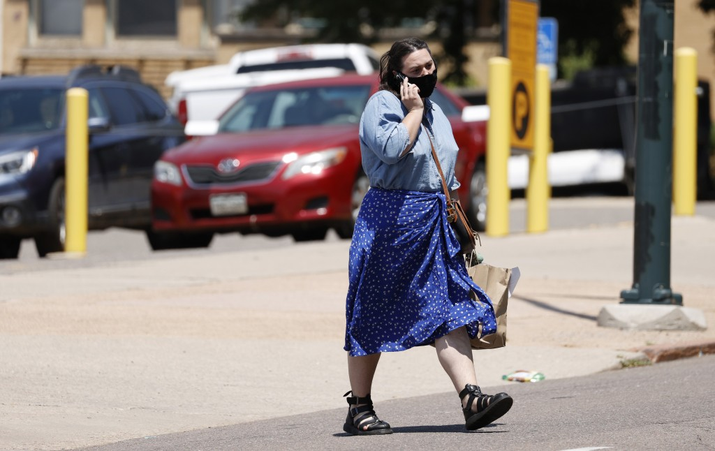 A pedestrian wears a face mask while chatting on a mobile device while crossing Grant Street near 8th Avenue Tuesday, July 21, 2020, in Denver. (AP Ph...