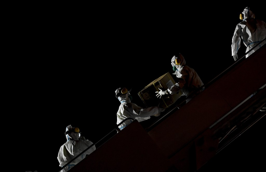 FILE - In this March 30, 2020, file photo, Venezuelan workers wearing protective face masks and suits as a preventive measure against the spread of th...